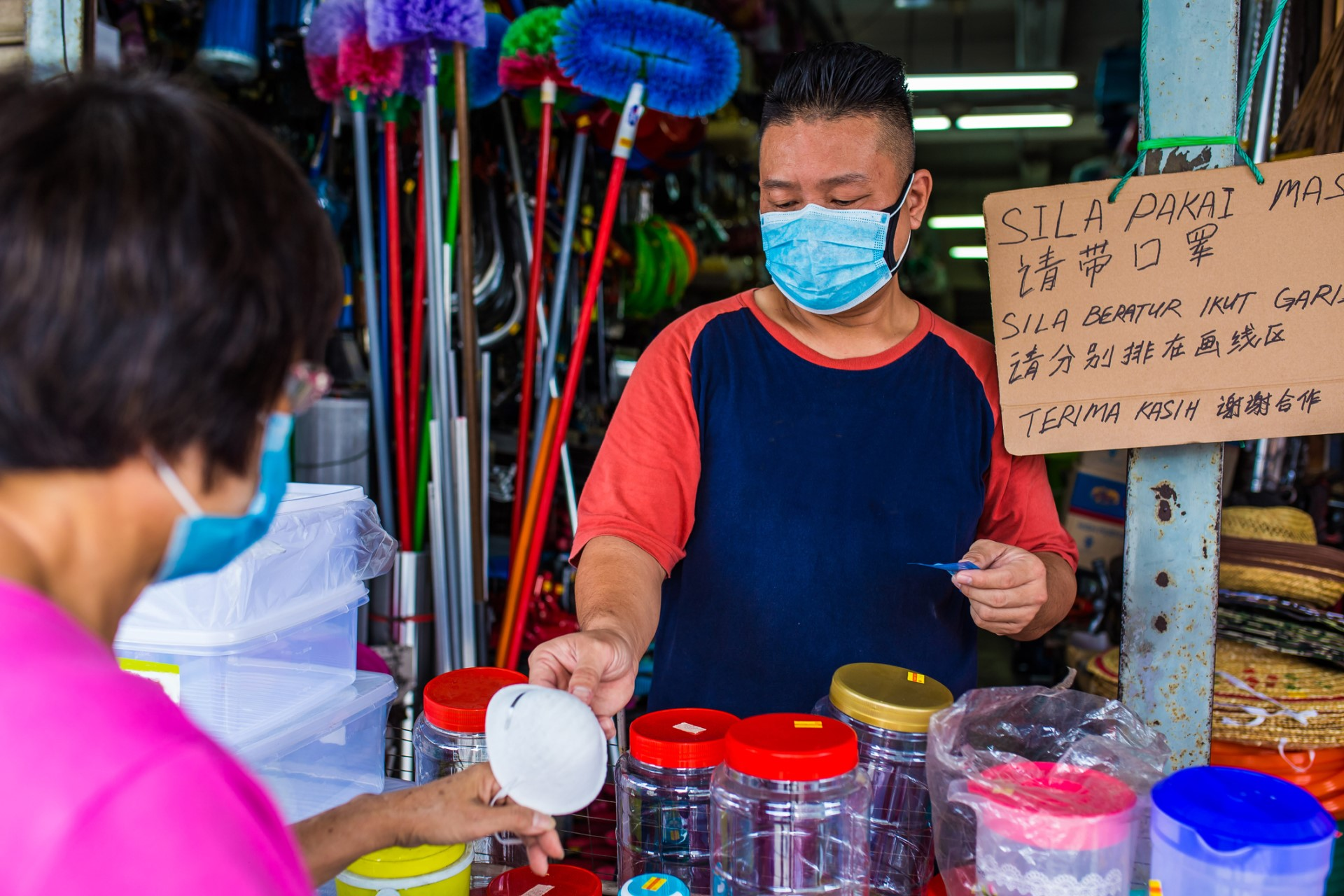 A shopkeeper asks customers to always wear a mask when buying from his store. Photo credit: iStock/Kong Ding Chek.