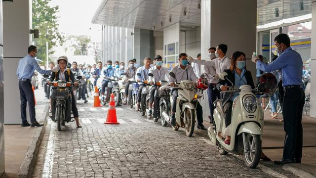 A line of motorcycle riders waiting to be tested